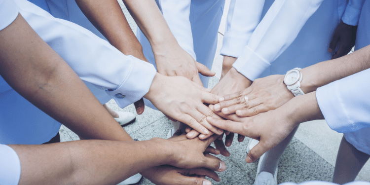 doctors and nurses stacking hands representing collaboration