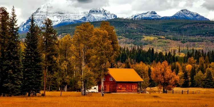 rural Colorado landscape with mountains and cabin